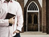 foto of front-entry  - Mixed Race man holding the bible in front of church - JPG