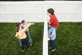 picture of pre-adolescents  - Mixed Race boys looking over fence at girls - JPG