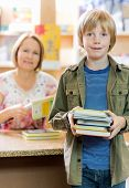pic of librarian  - Portrait of happy schoolboy checking out books from library with librarian in background - JPG