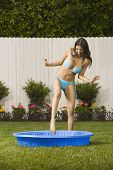 stock photo of kiddy  - Hispanic woman stepping into kiddie pool - JPG