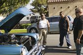 foto of 35 to 40 year olds  - Tattooed Hispanic men looking at car - JPG