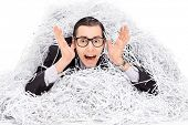 stock photo of terrifying  - Terrified man covered in a pile of shredder paper isolated on white background - JPG