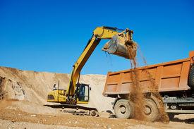 stock photo of boom-truck  - wheel loader excavator machine loading dumper truck at sand quarry - JPG