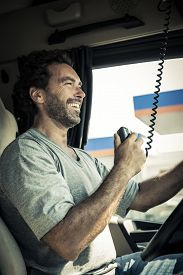 image of truck-stop  - Portrait of a truck driver using CB radio - JPG