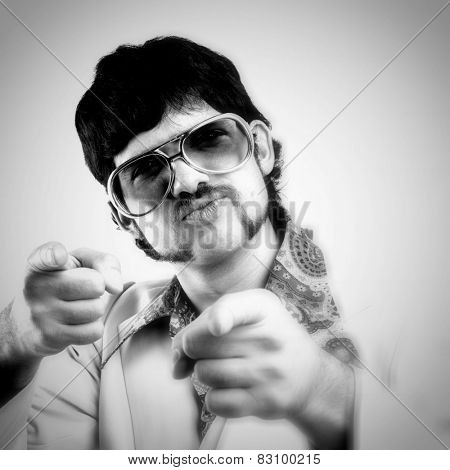 Instagram style portrait of a retro man in a 1970s leisure suit and sunglasses pointing to the camera - black and white