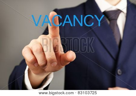 Businessman hand pushing Vacancy sign