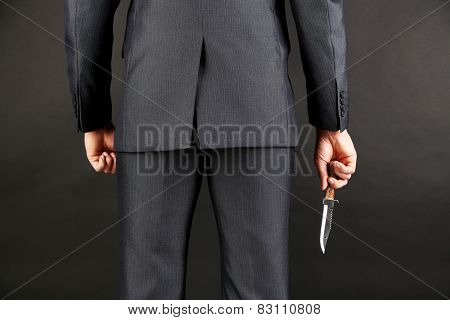 Businessman holding knife behind his back on gray background