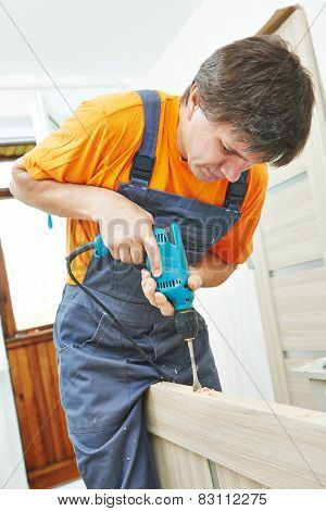 carpenter at interior wood door installation working with drill