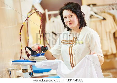 cleaning services. Woman with iron working at ironing shop