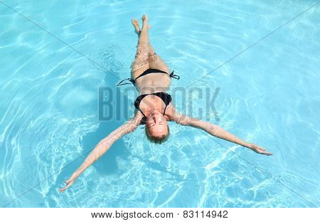 Caucasian lady floating in swimming pool.