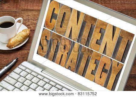 content strategy - text in letterpress wood type printing blocks on a laptop screen with cup of coffee