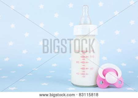 Baby milk bottle and pacifier on blue background