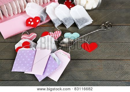 Heart shaped teabag tags on wooden background