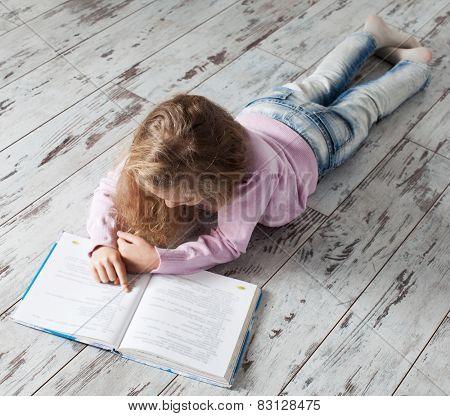 Child reading book at home. Girl doing homework