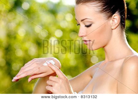 Woman Applying On Hand Cosmetic Cream