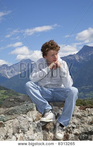 teenager sitting on a wall