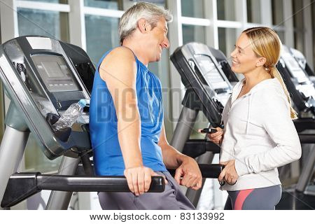 Two happy senior people in fitness center talking at a treadmill