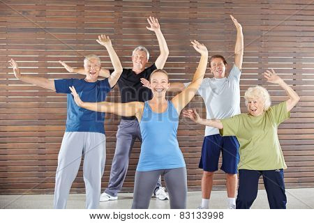 Group of happy seniors dancing and exercising in gym class