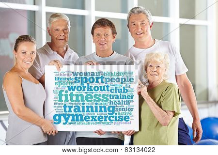 Senior people group holding fitness tag cloud in gym on cardboard sign
