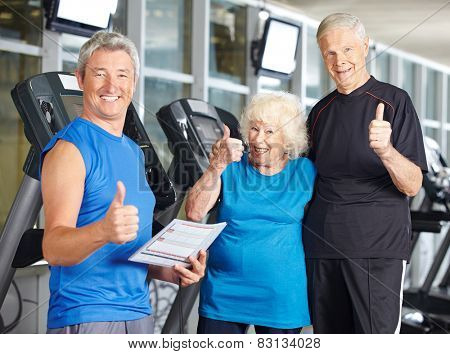 Happy senior couple in gym holding thumbs up with fitness trainer