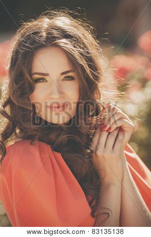 Beautiful woman in a summer garden blossoming roses.