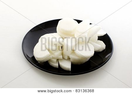 Daikon Radishes On Black Dish Isolated On White Background
