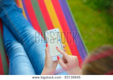 ZAPORIZHZHYA, UKRAINE - SEPTEMBER 20, 2014: Young Woman Using Google Web Search on her Smart Phone.