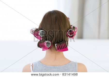 Back view portrait of a woman with curlers on her head