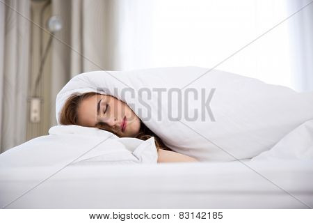 A young woman sleeping under a blanket