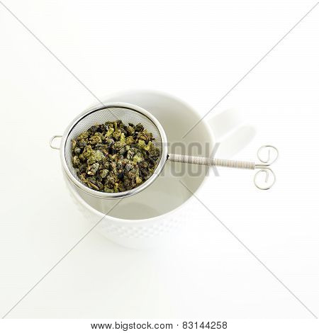 Herbal Tea In A Glass Cup, Metal Sieve With Dry Herbal Tea On A White Background