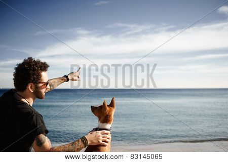 Caucasian Man In Sunglasses  Sitting In Beach In Spring Or Summer With Dog Breed Basenji Sitting In