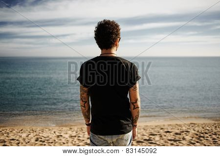 Brutal Man With Tattoos On Beach Standing In Sand Looking At Sea Enjoying Sun And Summer Travel Holi