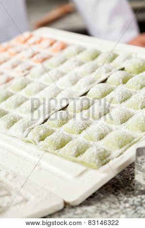 Raw ravioli pasta arranged on cutting board at commercial kitchen counter