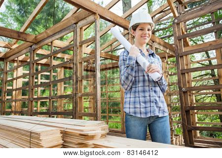 Portrait of smiling female engineer holding blueprint while standing in incomplete timber cabin at construction site