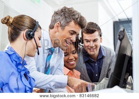 Manager with call center team using tablet PC in office