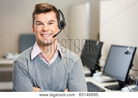 Portrait of confident male customer service representative with headset in call center