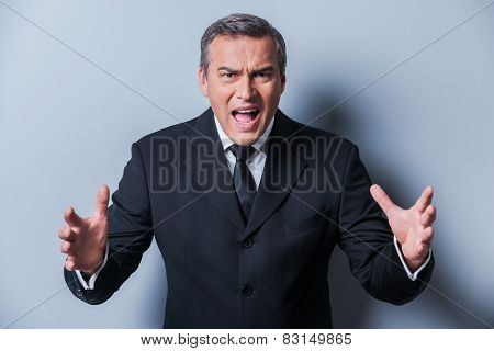 Furious Boss. Furious Mature Man In Formalwear Gesturing And Looking At Camera While Standing Agains