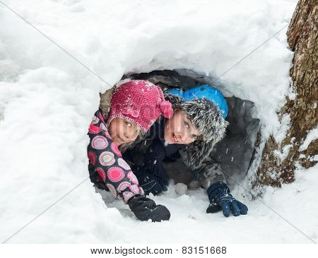 Young boy and girl hiding in a snow cave they made