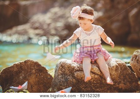 Adorable happy little girl playing on the rocks near the sea.