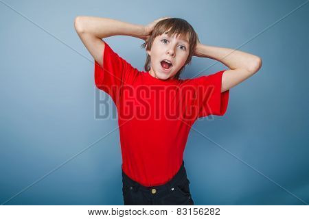 boy teenager European appearance in a red shirt put his hands be