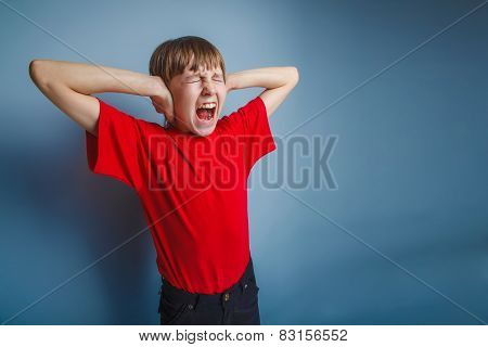 boy teenager European appearance in a red shirt covered his ears