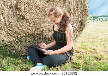 Girl With  Device Siting Close  To Haystack