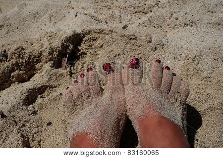 Female Feet With Red Pedicure In Beach