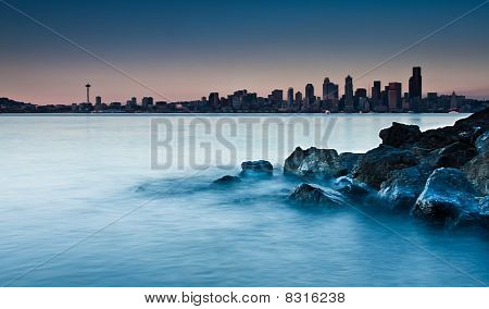 City Skyline From A Rocky Beach