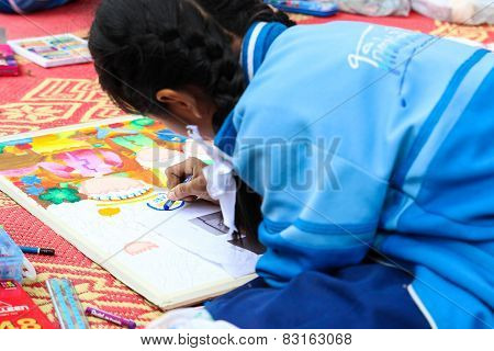 The Asian Girl Is Painting Crayon Color On Her Drawing For Drawing Contest.