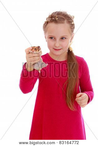 Charming girl playing with a hamster.