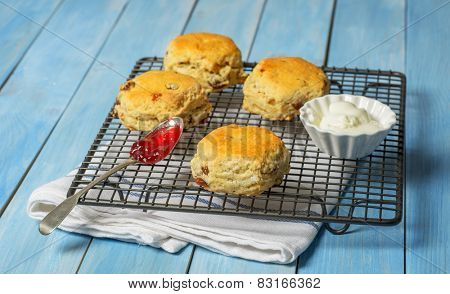 Freshly baked scones on cooling rack with fresh cream and spoonful of strawberry jam