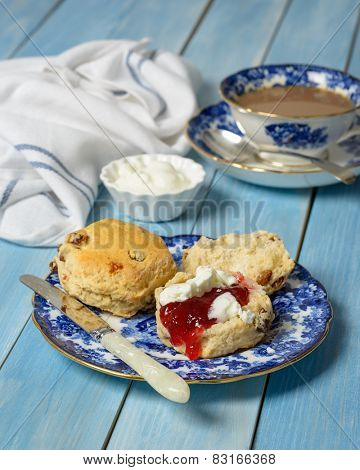Scones with jam and fresh cream on vintage plate with cup of tea in the background