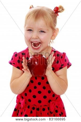 Happy laughing blond girl with a big red apple.
