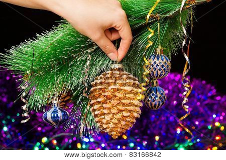 Close-up of woman hand hanging decorative toy pine cone on Christmas tree branch